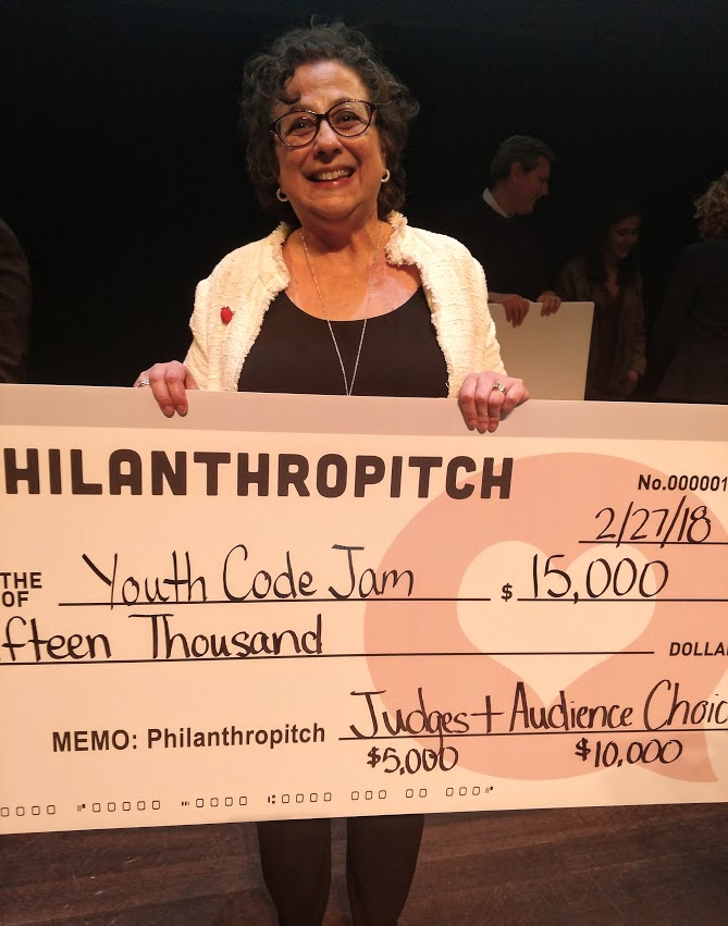 An image of Debi Pfitzenmaier, CEO of Youth Code Jam, holding a large check she won at the Philathropitch pitch competition for nonprofits.