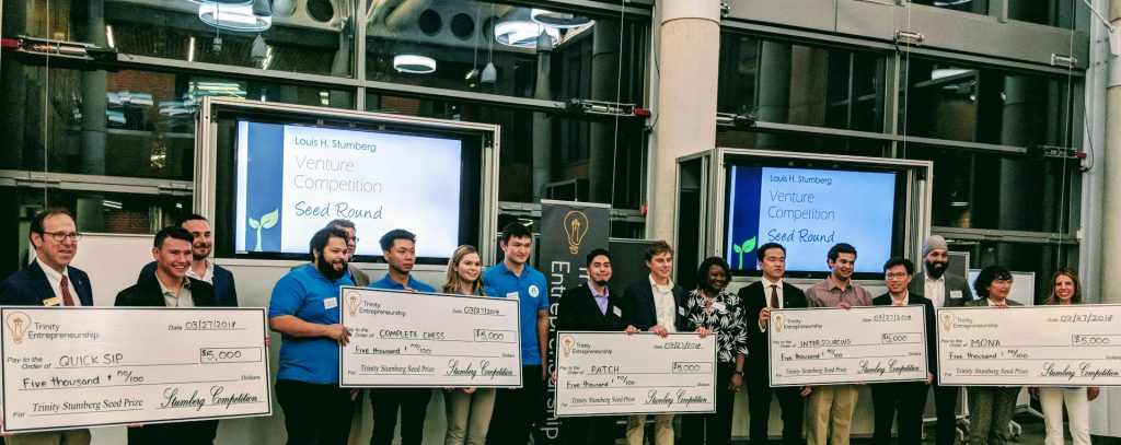 An image of five teams holding large award checks for $5,000