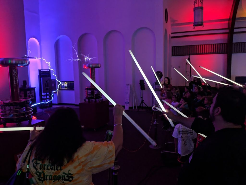 An image of two Tesla coils in front of a group of students