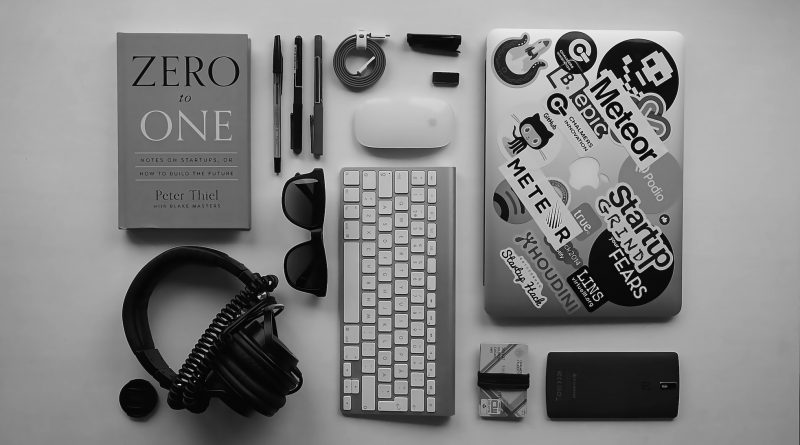 An image of a computer laptop, keyboard, headphones, and Zero to One book on startups