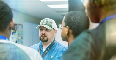 An image of SAMSOC co-founder Red Thomas talks to students training in cybersecurity.
