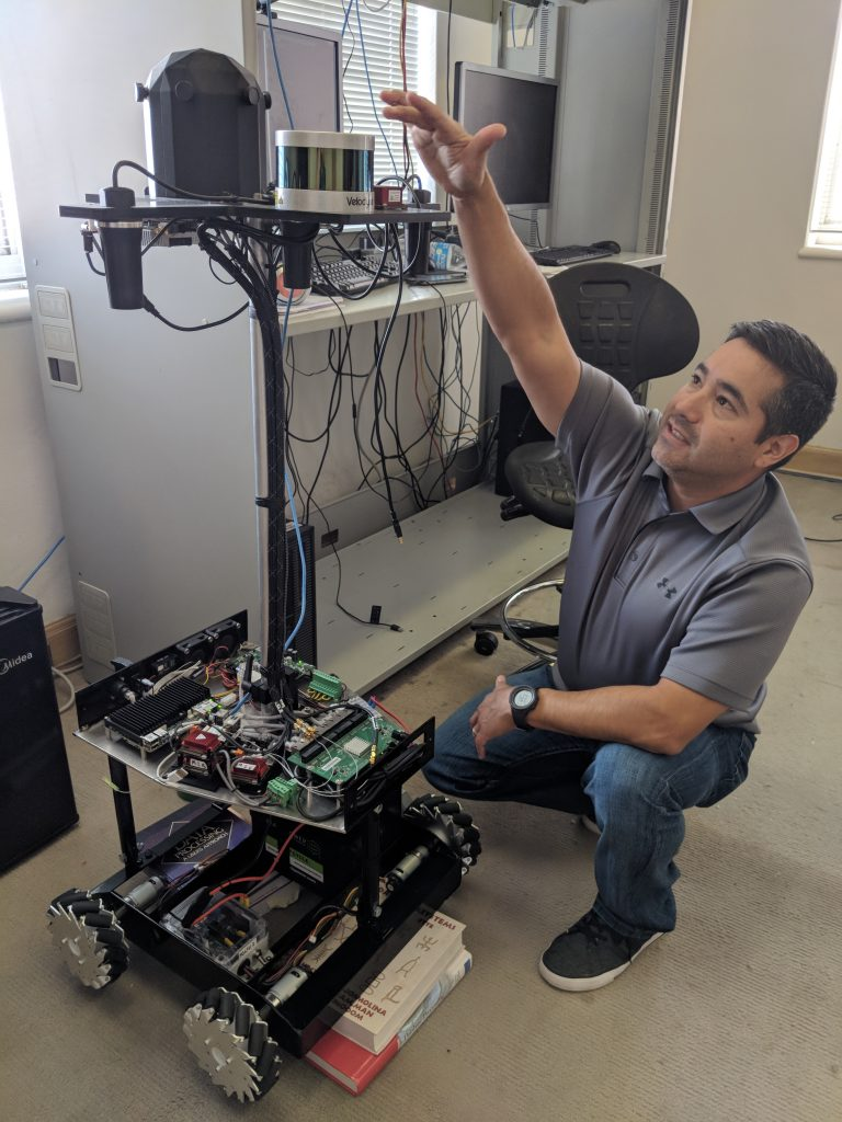 Reckon Point founder Gabe Garza points out features on an indoor GPS mapping robot. Photo credit: Startups San Antonio