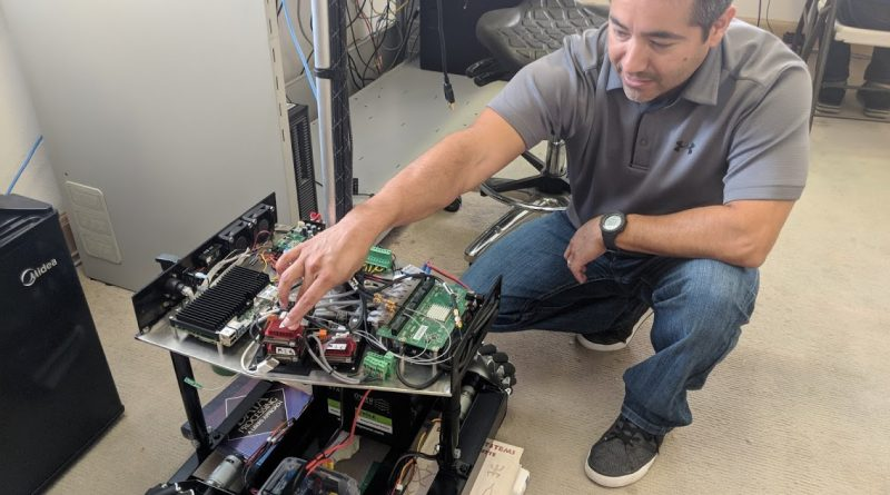 Gabe Garza points out features on the Reckon Point indoor GPS mapping robot. Photo credit: Startups San Antonio