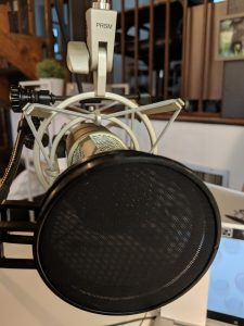 Closeup of an XLR microphone mounted on a boom arm for a podcast. Photo credit: Startups San Antonio.