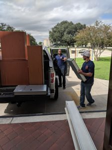 MoveIt founder Michael DeRouen (left) and mover Jared Fuller load items for a move from SAMSAT. Photo credit: Startups San Antonio.