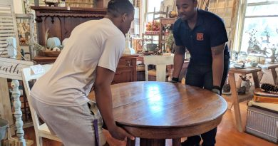 MoveIt owner Michael Rouen (right) and a mover move a table. Photo credit: Startups San Antonio.