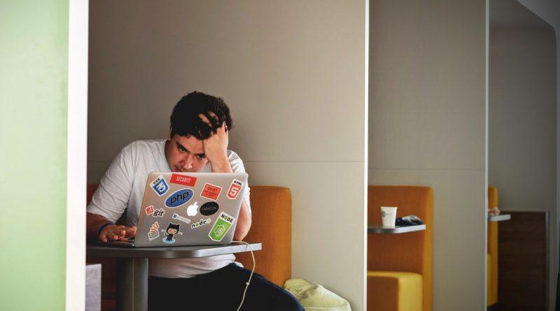 Startup founder struggles over laptop. Photo by Tim Gouw on Unsplash.