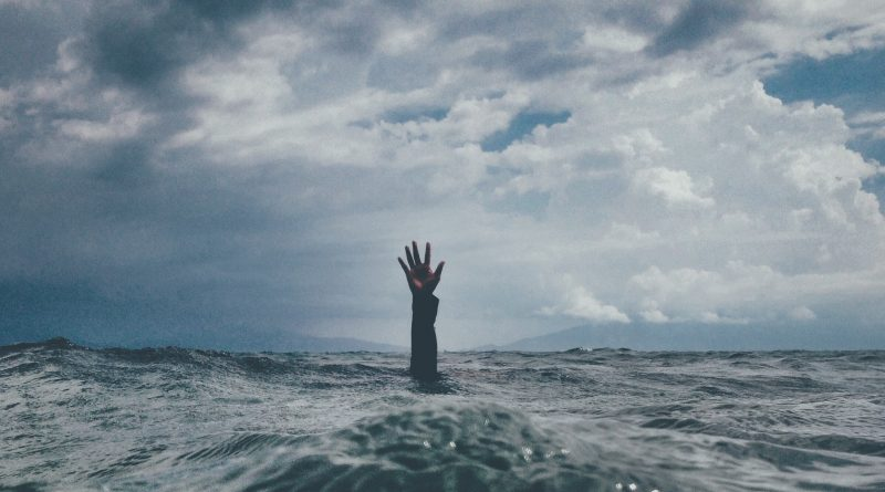 Image of a hand outstretched from a body of water. Photo by nikko macaspac on Unsplash.