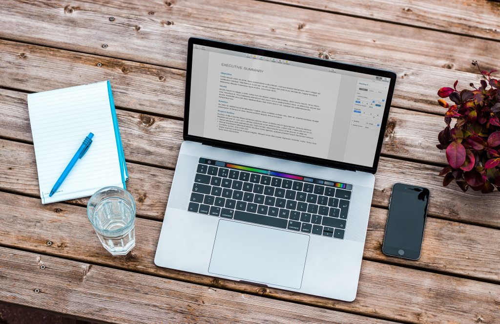 A laptop computer and cellphone on a desk. Photo by Bram Naus on Unsplash.