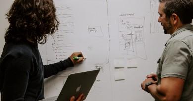 Two entrepreneurs at a whiteboard,discussing entrepreneurial success. Photo credit: Kaleidico on Unsplash.