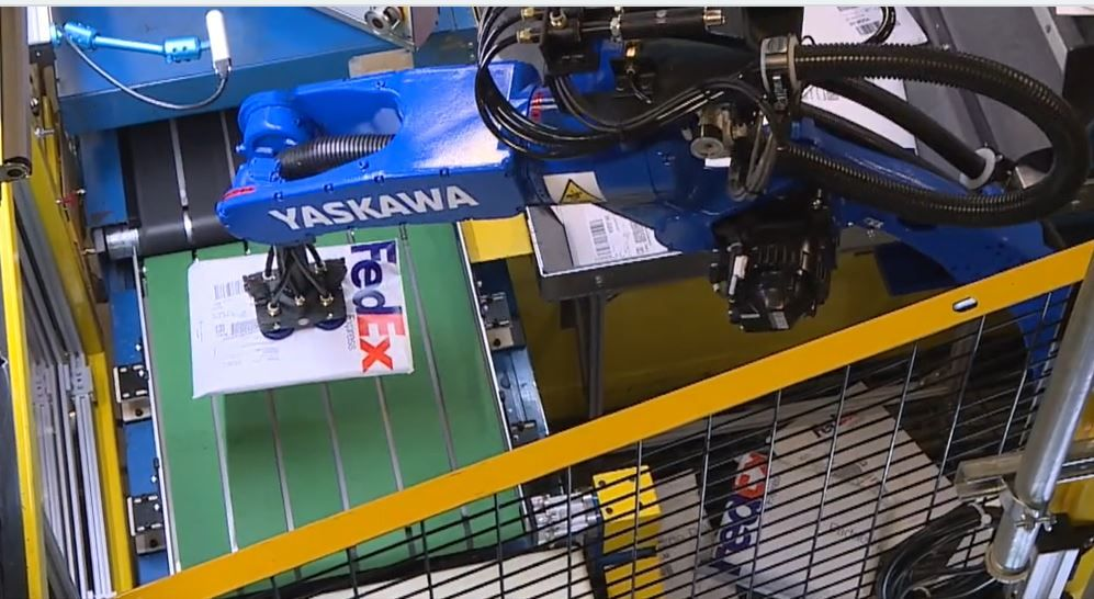 A Yaskawa robot picks up a package on a conveyor belt at plus One Robotics, courtesy photo