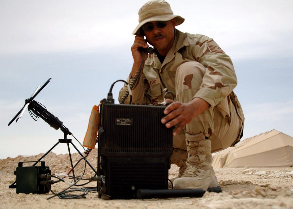 Master Sgt. Mike Rosado tests a multi-band satellite-communications-capable tactical radio used for secure tactical communications near Al Asad Air Base, Iraq. U.S. Photo credit: Air Force photo/Capt. Ken Hall.